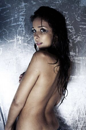 sexy model with wet and dirty skin and hair taking a shower photo
