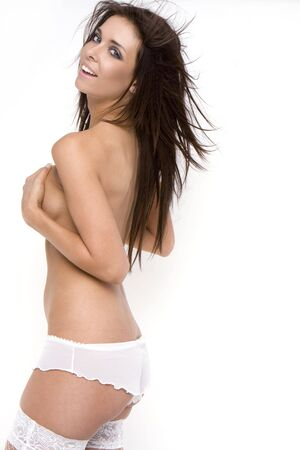 Attractive young woman implied topless wearing white lingerie and stockings smiling Stock Photo - 5752602