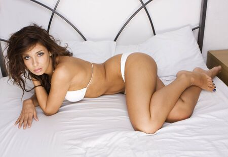 sexy brunette woman on the bed wearing white bikini  Stock Photo - 5752636