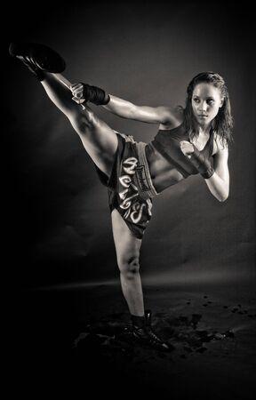 kickboxing:   Beautiful girl kicking with the leg black and white