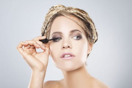 Young beautiful woman with healthy pure skin applying mascara on her lashes photo