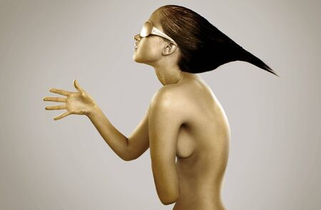 topless gold bodypainting on a brunette girl with a funky hairstyle Stock Photo - 5810783