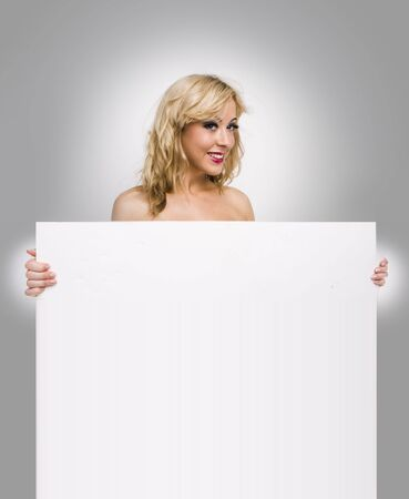 topless  girl holding blank sign board over white photo
