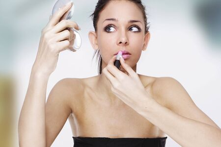 Beautiful young woman stressed before her date looking at the mirror applying makeup Stock Photo - 6184444