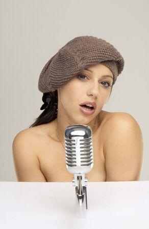Music star.Sexy woman singing in retro mic photo