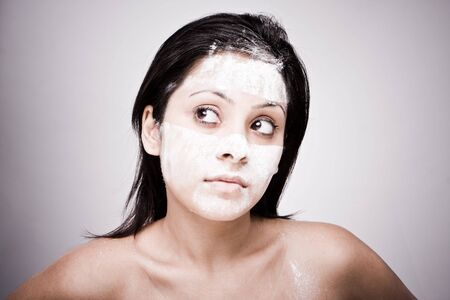 Portrait of the young brunette , Cosmetician make mask to girl. Facial massage. photo