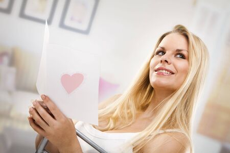 Woman reading a valentines card in living room  photo