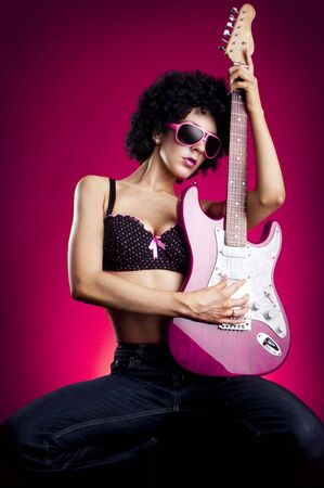 Beautiful high glamour fashion model in lingerie with a red Les Paul style electric guitar photo