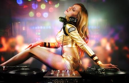 fiesta dj:  Bella chica de DJ en cubiertas tocando en el pueblo de partido en la pista de baile  Foto de archivo