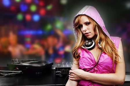 Beautiful DJ girl in pink standing in the front of the decks