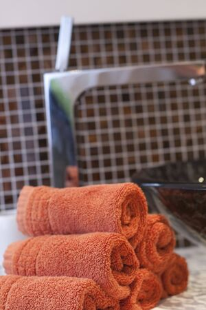 Beautiful sink in a bathroom with rolled up orange towels next to it  Stock Photo - 6276505