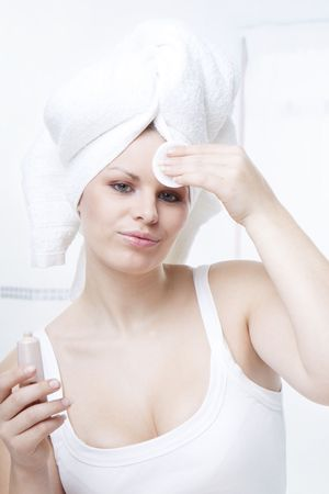 young beautiful woman cleaning face weraring a white towel on head Stock Photo - 6282664