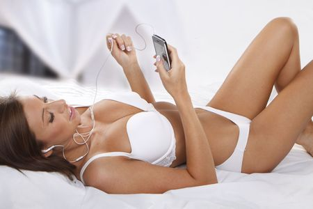 young beautiful woman listening music using mobile phone on bed photo