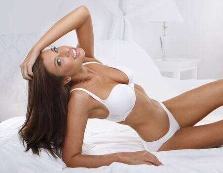 Portret studyjny młodych piękne kobiety na łóżko