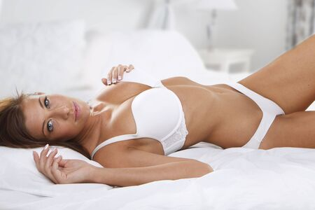 Studio portrait of young beautiful woman on bed photo