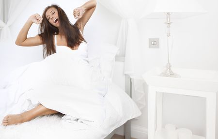 Young beautiful woman waking up in the morning in bedroom Stock Photo - 6336943