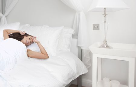 Young beautiful woman waking up in the morning in bedroom photo