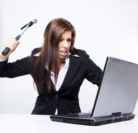 angry woman: angry business woman about to demolish her laptop with a hammer Stock Photo