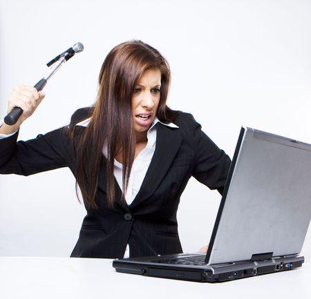Kobieta wściekły biznesowych ma do rozbiórka swojego laptopa młotkiem