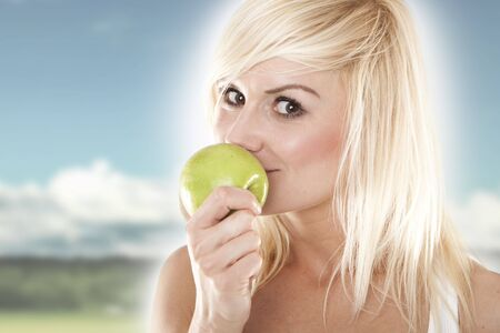 Closeup portrait of a lovely young blond holding a green apple outdoors photo