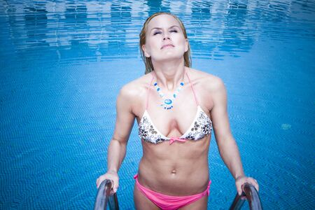 Sexy  woman in a light clear blue swimming pool, climbing the stairs to get out of the pool. She is wearing a pink bikini and is holding herself onto the stainless steel stairs while water is dripping from her hair and body. Stock Photo - 6538372