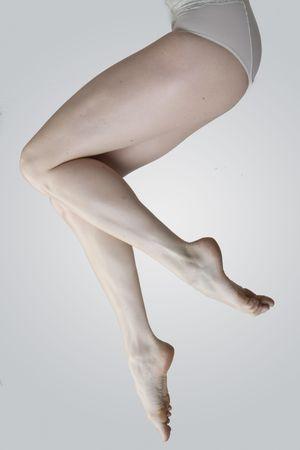 Beautiful woman legs on grey background photo