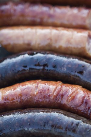 Delicious grilled sausages and black puddings  closeup photo