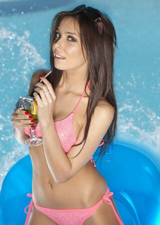 Stunningly beautiful young sexy brunette woman in drinking a cocktail by a blue swimming pool Stock Photo - 6727769