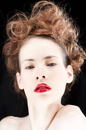Portrait of woman wearing red lipstick isolated against a black background. photo