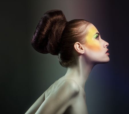 A portrait of a glamorous woman with a creative orange makeup on the sides of her face. Фото со стока