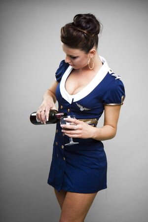 pours: Sexy young air stewardess pouring drink from wine bottle, studio background.