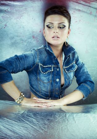 Sexy brunette woman wearing short denim jacket, jeans with belly button ring, bracelet, and hoop earrings against a graffiti covered wall.