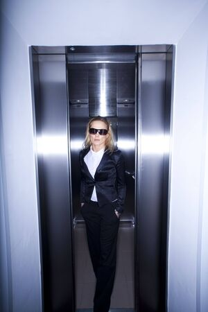 Young business woman wearing glasses using elevator at office. photo