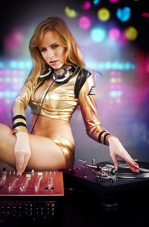 Beautiful DJ girl on decks on the party with the disco light on the background Stock Photo