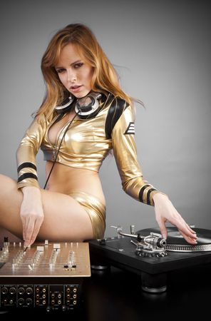 Beautiful DJ girl on decks on the party with the plain gray background