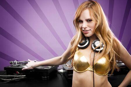 Beautiful DJ girl on decks wearing gold and headphones photo