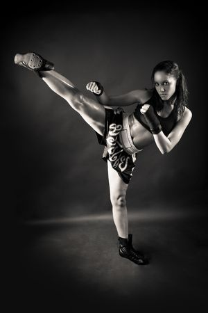 Beautiful girl kicking with the leg on black background photo