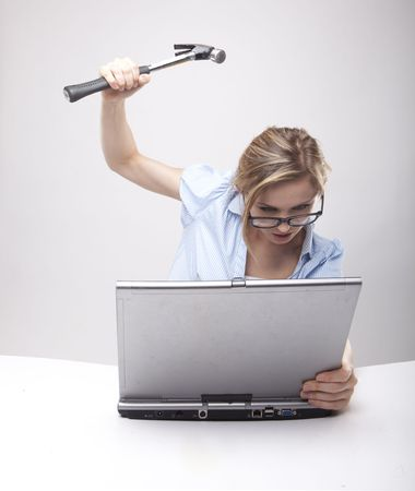 Attractive blond hair woman wearing business suit sitting in front of a computer with angry facial expression holding a hammer and wearing glasses