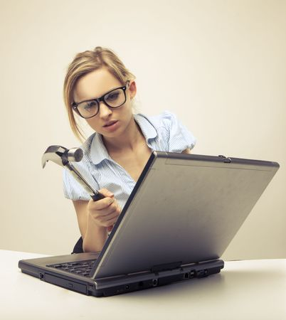 Attractive blond hair woman wearing business suit sitting in front of a computer with angry facial expression holding a hammer and wearing glasses photo