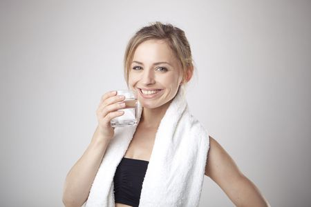 Woman Drinking Water wearing sportswear and towel  photo
