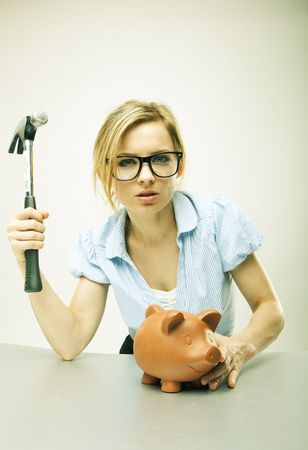 Young woman breaking a piggy bank photo