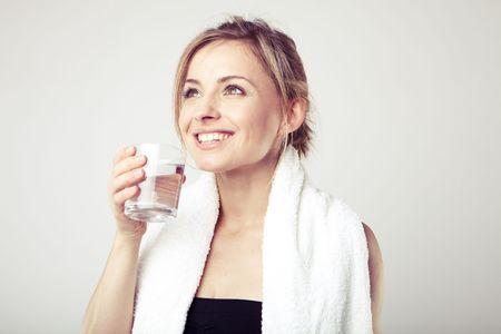 Woman Drinking Water wearing sportswear and towel