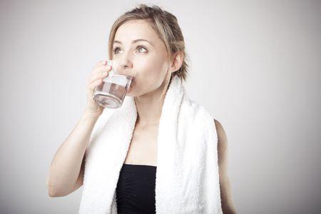 Agua potable de mujer vistiendo ropa deportiva y toalla