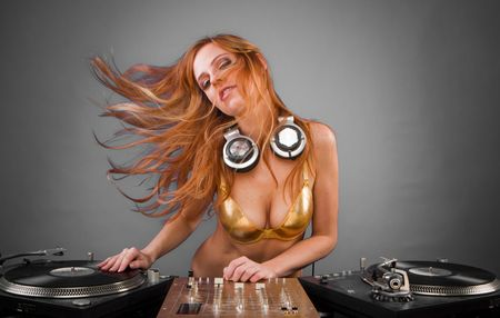 entertainment:  Beautiful DJ girl on decks on the party with the plain gray background