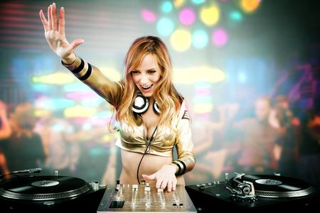 party girl:  Beautiful DJ girl on decks on the party with the disco light on the background Stock Photo