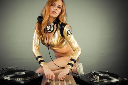 fiestas discoteca: Bella joven DJ sobre cubiertas en el partido con el fondo liso  Foto de archivo