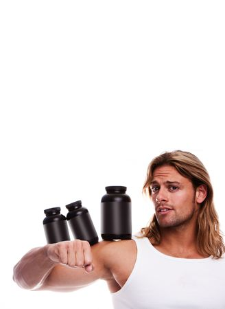 Athletic sexy male body builder holding a boxes with supplements on his biceps