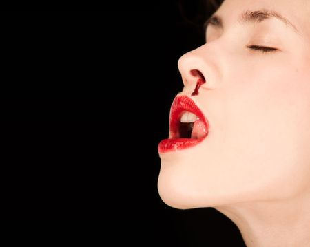 Portrait of a pale woman wearing red lipstick and a bloody nose isolated against a black background. photo
