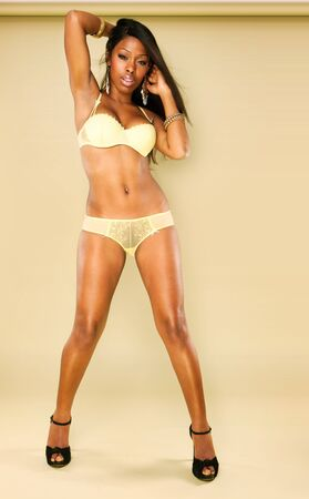 Sexy African American young woman wearing erotic yellow lingerie