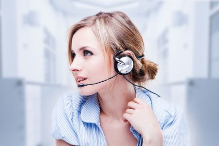 telephone headsets: Attractive Blond Young Woman With A Telephone Headset